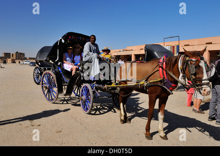Tourists in horse drawn carriage at Temple of Horus -  Edfu, Upper Egypt - Stock Photo