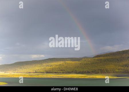 Heavy clouds and rainbow over Marsh Lake, headwaters of the Yukon River, near Whitehorse, Yukon Territory, Canada - Stock Photo