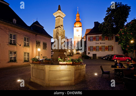 Maximilian Fountain in Alter Markt square with the old town hall and the bell tower at dusk, Arnsberg, Sauerland - Stock Photo