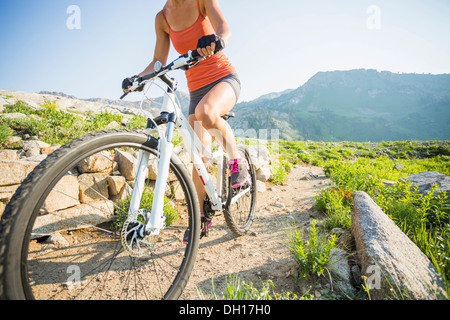 Caucasian woman riding mountain bike on rocky trail - Stock Photo