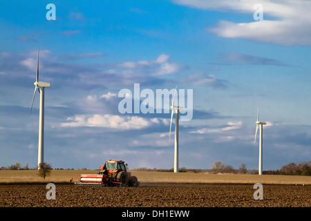 Tractor plowing a field, wind turbines in background, Denmark, Europe - Stock Photo
