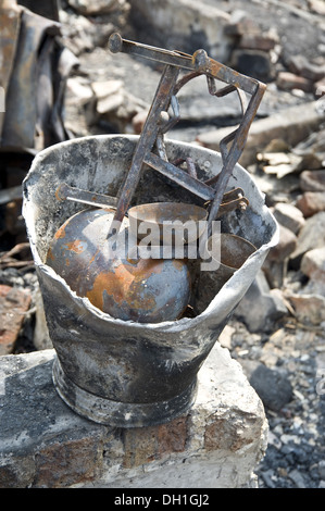 damaged destroyed things in bucket after fire bandra slums mumbai Maharashtra India Asia - Stock Photo