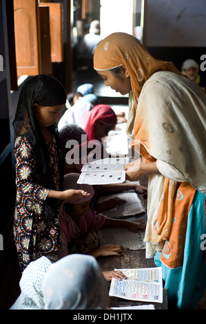 Muslim teacher with children in classroom at Islamic school uttar pradesh India Asia - Stock Photo