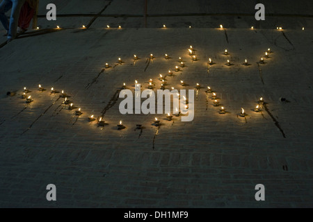 oil lamps diyas in the shape of OM diwali festival varanasi uttar pradesh India - Stock Photo