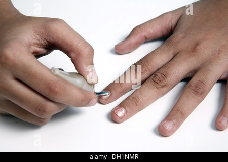 Young girl woman applying nail polish on finger close up of fingers and nail polish brush   MR#743AC - Stock Photo