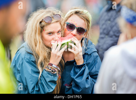 The Reading Festival - three girls sharing a slice of melon UK 2013 - Stock Photo