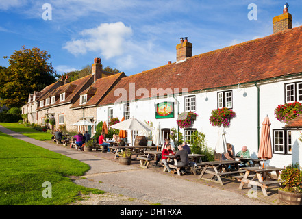 People sat outside The Tiger Inn on the village green East Dean East Sussex England UK GB EU Europe - Stock Photo