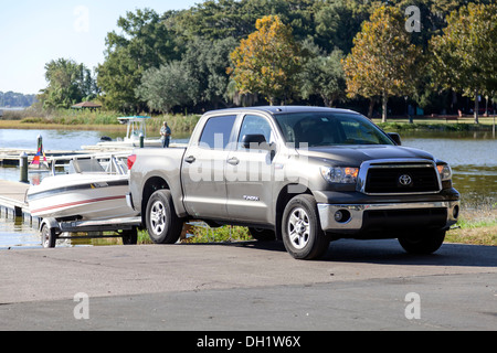 A silver Toyota Tundra extended king cab pick-up truck towing a small speedboat on a trailer at public boat ramp - Stock Photo