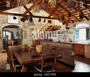 Rustic wooden table and chairs in dining area of large Spanish kitchen with dried flowers hanging from wooden ceiling - Stock Photo