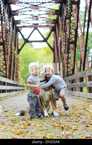 two young children, a boy and his baby brother as standing outside on a bridge in the woods, lovingly hugging their - Stock Photo