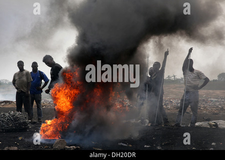 Teenage boys burn cables from computers and other electronics to recover copper near the Agbogbloshie slum in Accra, - Stock Photo