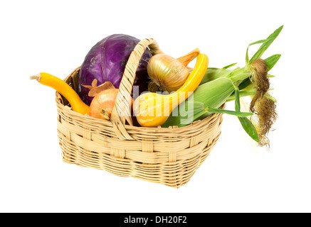 A large wicker basket filled with freshly picked assorted garden vegetables on a white background. - Stock Photo