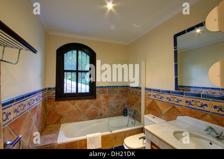 Window above bath in Spanish bathroom with traditional terracotta ...