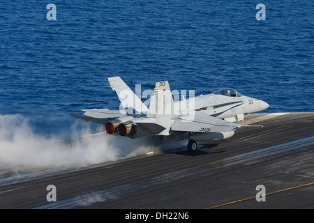 An F/A-18C Hornet assigned to the Blue Diamonds of Strike Fighter Squadron (VFA) 146 launches from the flight deck - Stock Photo