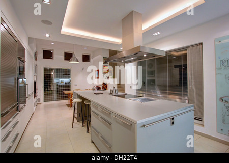 Extractor above hob in island unit in large modern Spanish apartment kitchen with fluorescent lighting on recessed - Stock Photo