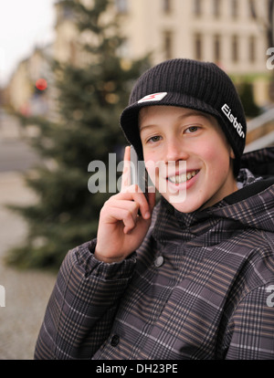 Boy, 12 or 13 years, with mobile phone, PublicGround - Stock Photo