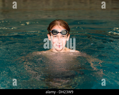 Boy, swimmer, 12 or 13 years, with swimming goggles in a swimming pool - Stock Photo