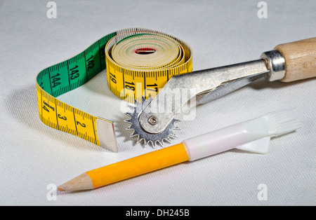 Seam roller, tape measure and white tailor's chalk lying on linen fabric