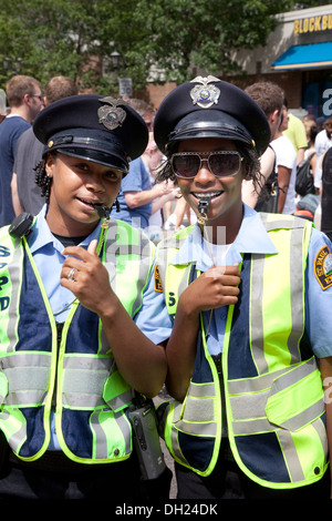 Two happy black police women directing traffic with whistles at Grand Old Day Festival St Paul Minnesota MN USA - Stock Photo