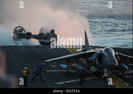 Air department personnel approach an AV-8B Harrier while a landing craft air cushion attached to Amphibious Craft - Stock Photo