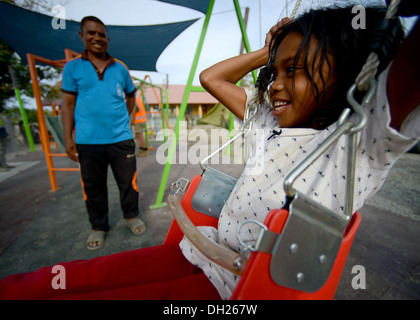 METINARO, Timor-Leste – (Oct. 26, 2013) Arrita, a local Timorese girl, takes the first swing on a completed playground - Stock Photo