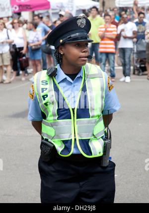 Black police woman calmly directing traffic. Grand Old Day Festival St Paul Minnesota MN USA - Stock Photo