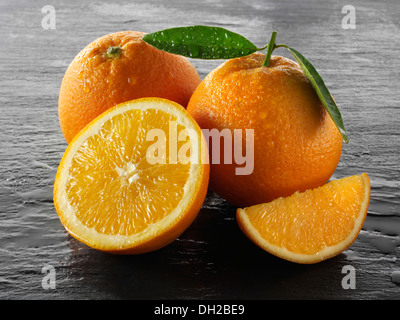 Whole and cut fresh oranges with leaves - Stock Photo