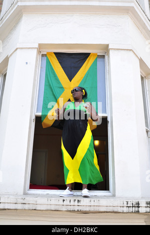 A woman wearing a Jamaican flag dress at the Notting Hill Carnival, London - Stock Photo