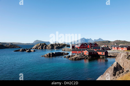 Red fishermen's houses, called rorbuer, holiday resort in Mortsund with aquaculture fish farming, Mortsund, Lofoten, - Stock Photo