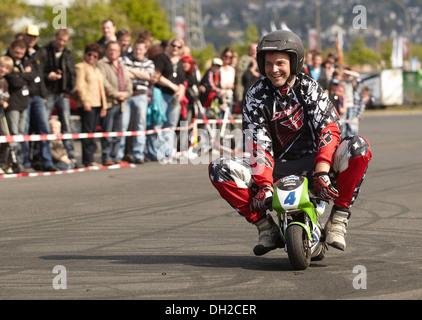 Motorcycle stuntman Mike Auffenberg riding a pocket bike, Koblenz, Rhineland-Palatinate - Stock Photo