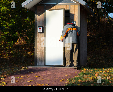 Man going into an outhouse loo outdoor privy. - Stock Photo