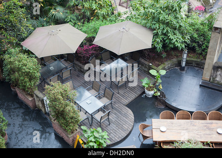 house patio with table and chairs under umbrella, there are a lot of vegetation around. - Stock Photo