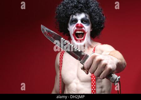 Evil Spooky Clown Portrait Holding Knife - Stock Photo