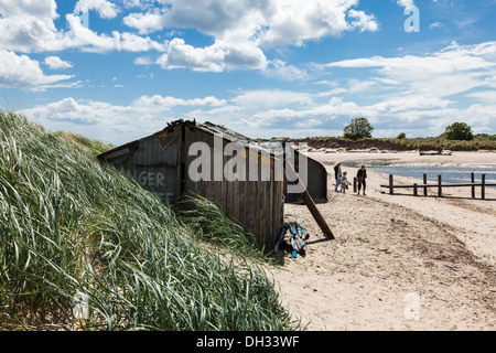A family passes the Nordic style huts on the beach at Alnmouth, Northumberland, UK - Stock Photo