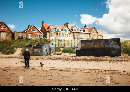 Dog walker passes the Nordic style huts on the River Aln at Alnmouth, Northumberland, UK - Stock Photo