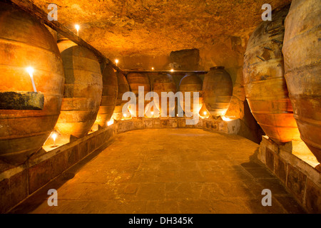 Antique winery in Spain with clay vessels terracotta amphora pots Mediterranean tradition with candlelight - Stock Photo