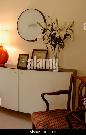 Detail of a living room with designer sideboard or cabinet family photographs a large wall clock, vase of flowers - Stock Photo