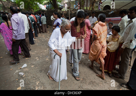 Young girl helping old women senior citizen with walking stick to vote Mumbai Maharashtra India Asia Oct 2009 - Stock Photo