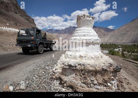 Indian Army vehicle passes Buddhist stupa on the Leh road, high in the Himalayas, Hunder, Ladakh, India - Stock Photo