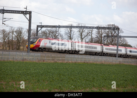 A Virgin passenger train on the West Coast Main Line. - Stock Photo