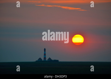 Sunset behind the Westerheversand Lighthouse, Westerhever, North Frisia, Schleswig-Holstein, northern Germany - Stock Photo