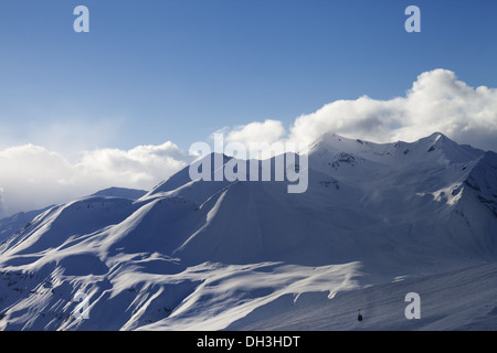 View on ski slope and sunlight mountains in evening. Ski resort Gudauri. Caucasus Mountains, Georgia. - Stock Photo