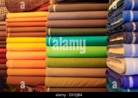 Reels of brightly colored cotton cloth in a stack. - Stock Photo