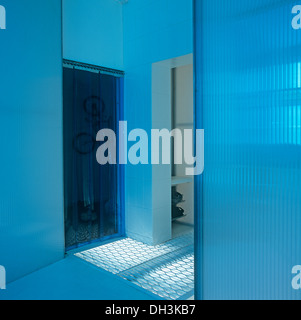 Glass wall in modern blue hall with thick blue plastic curtain on door - Stock Photo