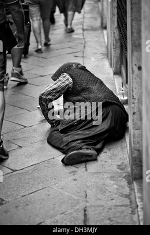 Beggar lying on a street, black and white, Venice, Veneto, Italy, Europe - Stock Photo