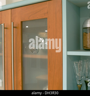 Close-up of modern kitchen cupboard doors with engraved opaque glass panel - Stock & Close-up of kitchen cupboard with opaque glass doors with steel ...