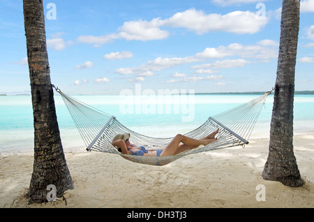 Happy woman relaxing on hammock on the beach during travel vacation on tropical island in Aitutaki lagoon, Cook - Stock Photo