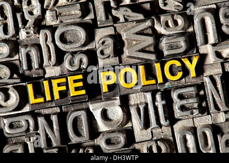 Old lead letters forming the words Life Policy - Stock Photo