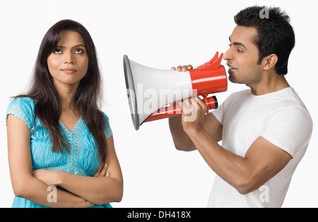 Side profile of a young man blowing a bullhorn with a teenage girl standing beside him - Stock Photo