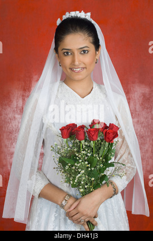 Portrait of a newlywed bride holding a bouquet of flowers and smiling - Stock Photo
